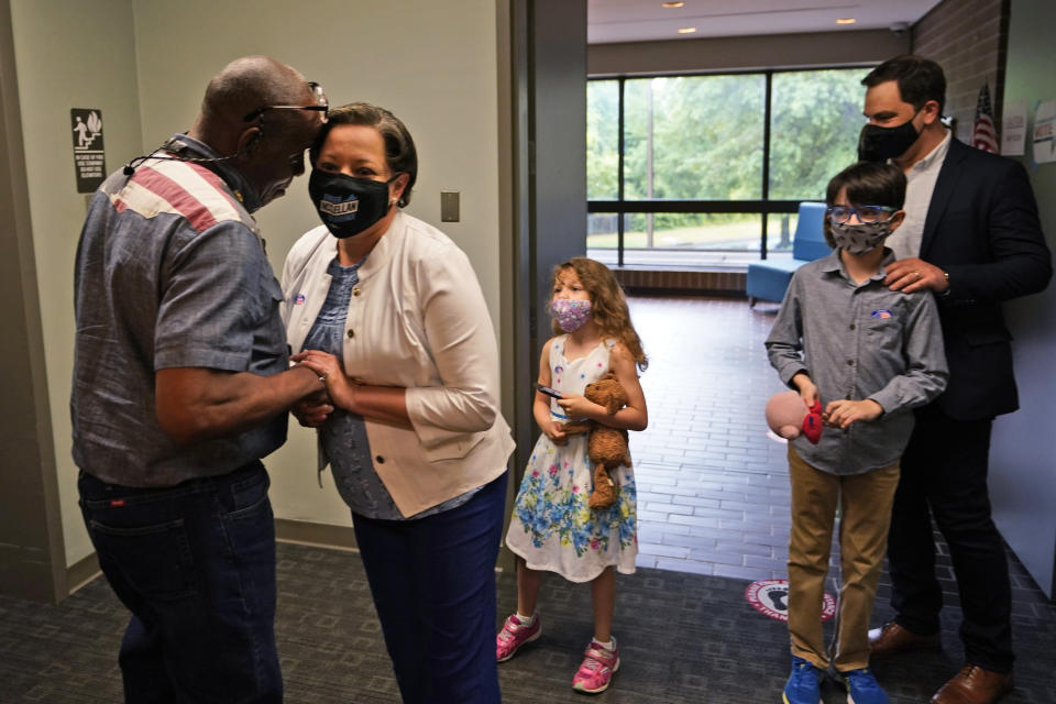 Democratic gubernatorial candidate, Virginia State Sen. Jennifer McClellan, second from left, greets a voter at an early voting location as her family looks on in Richmond, Va., Saturday, May 29, 2021. McClellan faces four other Democrats in the primary. (AP Photo/Steve Helber)