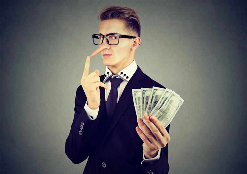 Liar young business man in suit and glasses with dollar cash. Source: Getty