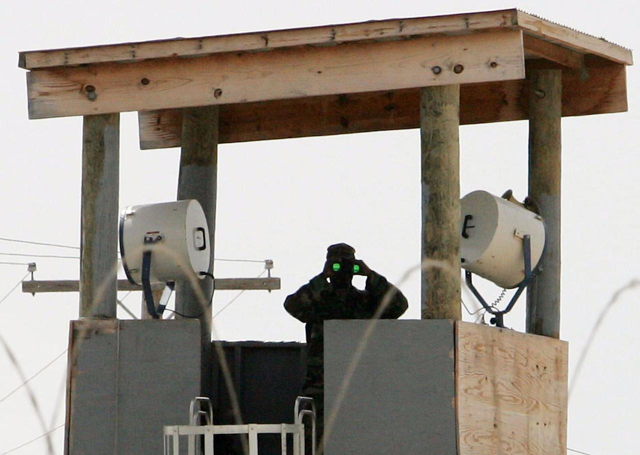 A U.S. Army soldier stands watch in a guard tower at Camp Delta at Guantanamo Naval Base August 23, 2004 in Guantanamo, Cuba. Four suspected al Qaeda fighters will be formally charged with war crimes this week as the U.S. military opens the first legal hearings for foreign prisoners captured during the war in Afghanistan and held at a remote U.S. Navy base in Cuba. Beginning on Tuesday, the prisoners from Australia, Sudan and Yemen will appear separately, unshackled and in civilian clothing before a panel of five U.S. officers who will read the charges against them at the arraignments, officials at the Guantanamo base said on Sunday. REUTERS/Mark Wilson/Pool  JDP
