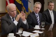 FILE - In this Thursday, Jan. 23, 2014, file photo, Vice President Joe Biden, left, speaks during a meeting with U.S. mayors including Louisville, Ky. Mayor Greg Fischer, center, to discuss workforce development, in the Roosevelt Room of the White House in Washington. As Congress was debating a massive COVID-19 relief plan earlier in 2021, some governors and mayors pleaded that a federal infusion of money was needed immediately to help their communities recover. Now that they got it, some state and local officials are taking their time before actually spending the windfall. (AP Photo/Jacquelyn Martin, File)