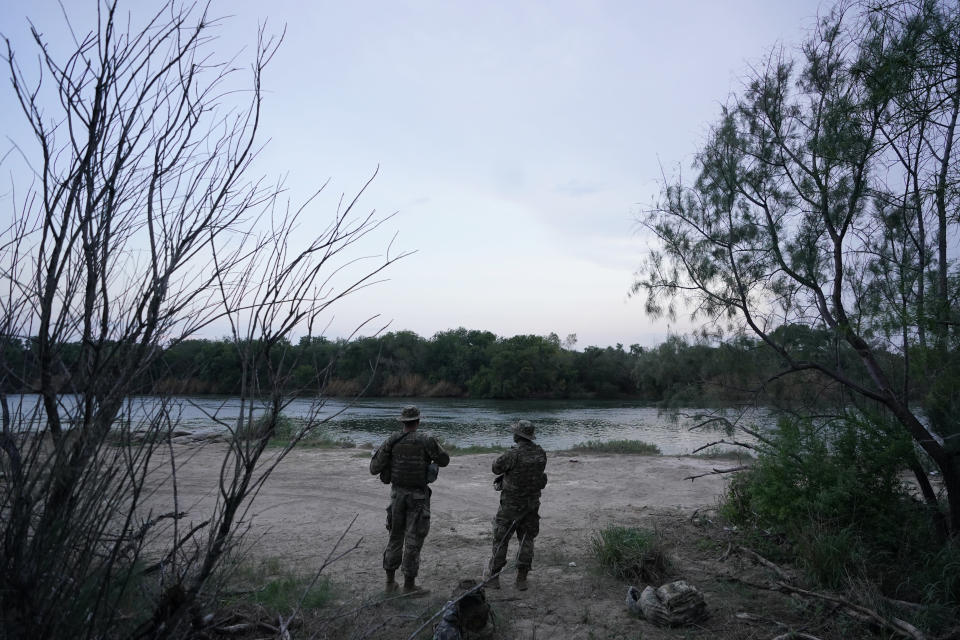 Members of the Texas Military Department stand guard along the U.S.-Mexico border Tuesday, May 11, 2021, in Roma, Texas. The U.S. government continues to report large numbers of migrants crossing the U.S.-Mexico border with an increase in adult crossers. But families and unaccompanied children are still arriving in dramatic numbers despite the weather changing in the Rio Grande Valley registering hotter days and nights. (AP Photo/Gregory Bull)
