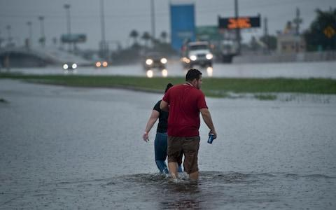People walk through flooded streets during the aftermath of Hurricane Harvey - Credit: BRENDAN SMIALOWSKI/AFP/Getty