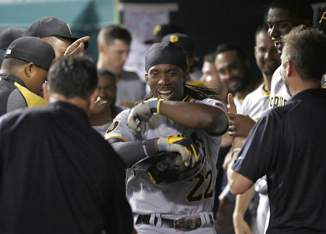 Pittsburgh Pirates' Andrew McCutchen is congratulated by teammates in the dugout after hitting a solo home run off Cincinnati Reds relief pitcher J.J. Hoover in the 11th inning of a baseball game, Saturday, July 12, 2014, in Cincinnati. The Pirates won 6-5 in 11 innings. (AP Photo/David Kohl)