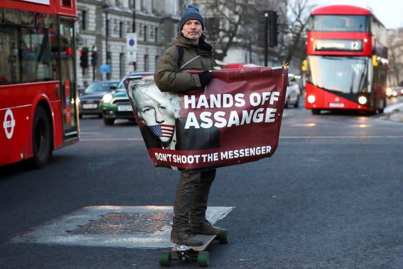 FILE PHOTO: A man rides a skateboard holding a banner with an image of Julian Assange in London
