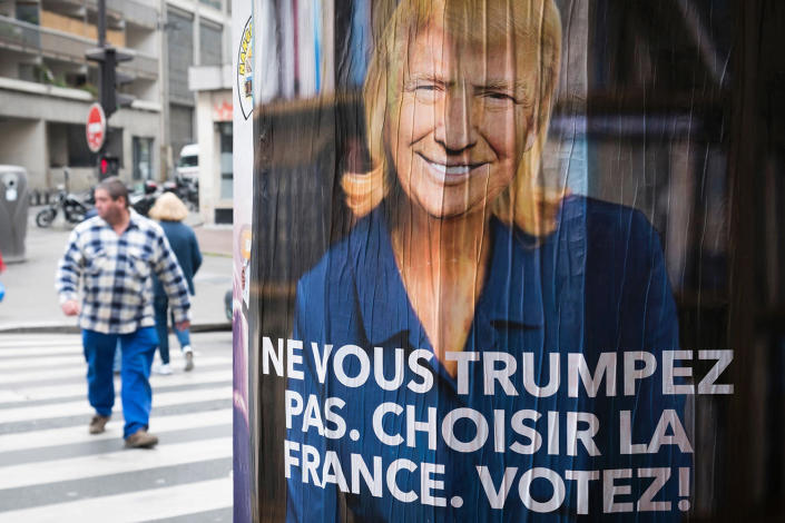 """<p>A man passes a poster depicting French presidential election candidate for the far-right Front National (FN) party Marine Le Pen with the face of U.S. President Donald Trump reading """"Do not Trump yourself. Choose France. Vote!"""" on May 5, 2017 in Paris. (Photo: Joel Saget/AFP/Getty Images) </p>"""