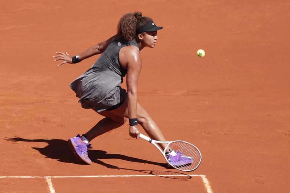 Naomi Osaka of Japan returns the ball to Karolina Muchova of the Czech Republic during their match at the Madrid Open tennis tournament in Madrid, Spain, Sunday, May 2, 2021. (AP Photo/Paul White)
