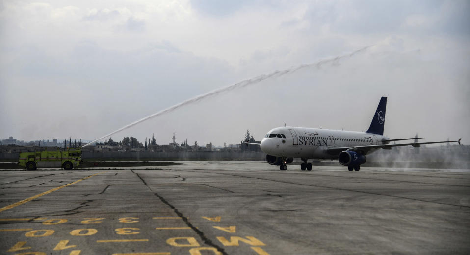 This photo released by the Syrian official news agency SANA, shows a Syrian commercial plane carrying Syrian officials and journalists, being met with a water cannon salute after it landed at Aleppo Airport, Syria, Wednesday, Feb. 19, 2020. The Syrian commercial flight on Wednesday from Damascus, marked the resumption of internal flights between Syria's two largest cities for the first time since 2012. (SANA via AP)