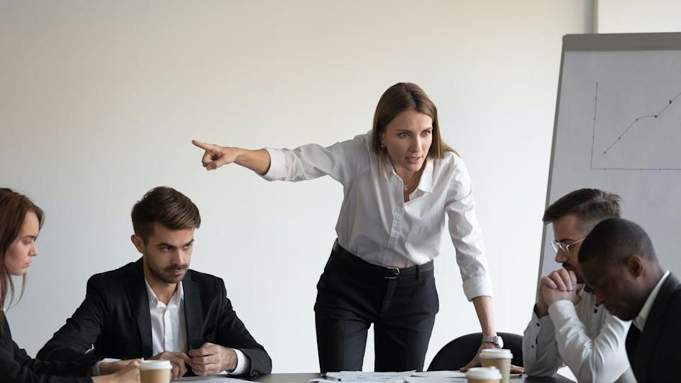 A woman boss yells at her employees in a meeting room.