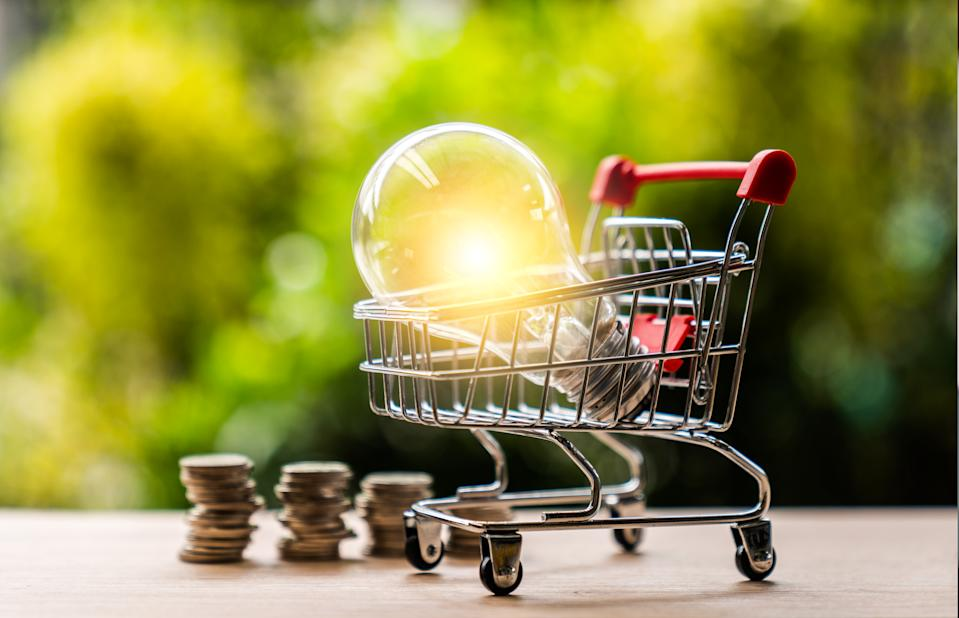 Led lamp and glowing light bulb in mini shopping cart or trolley with money coins against blurred natural green background for finance, saving energy and environment concept