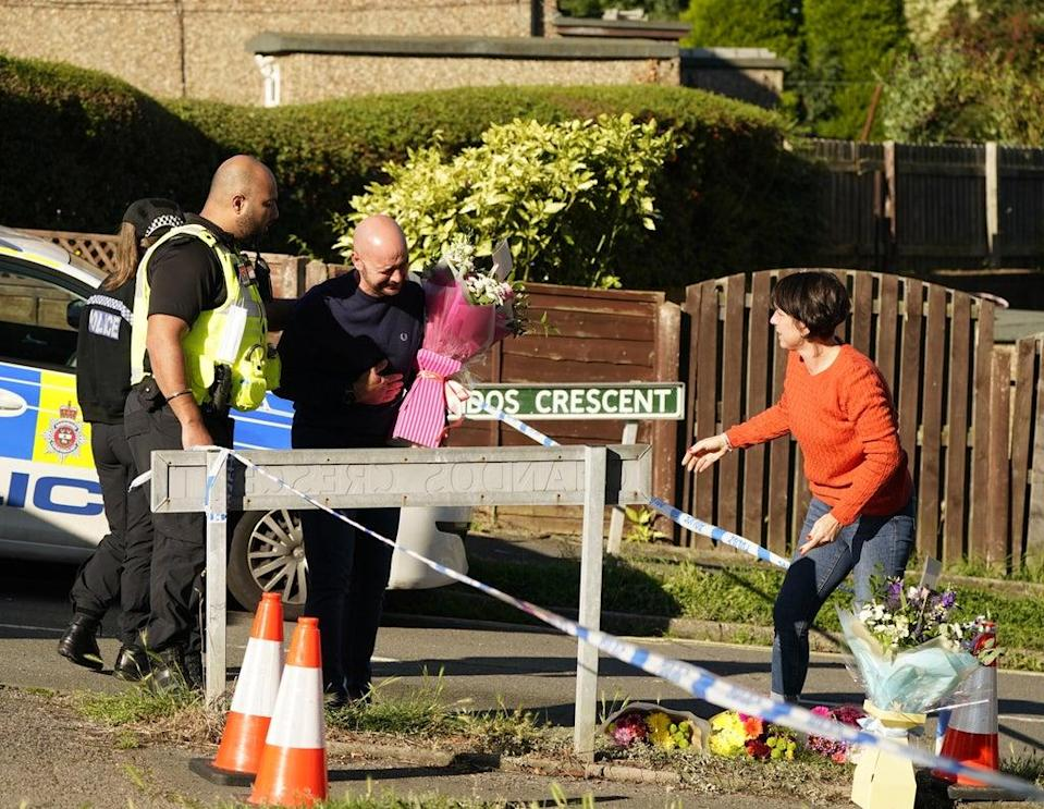 The father to some of the victims leaves flowers at the scene in Chandos Crescent (Danny Lawson/PA) (PA Wire)