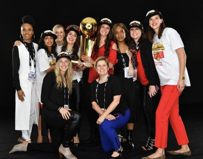 Toronto Raptors female staff pose with Larry O'Brien trophy