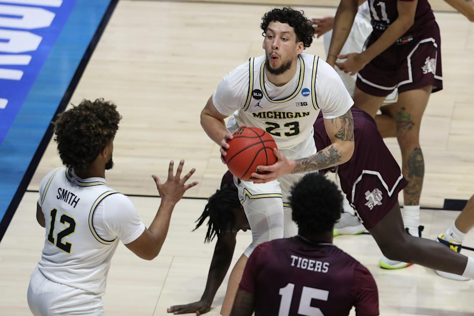 Michigan's Brandon Johns Jr. passes the ball to guard Mike Smith after pulling down a rebound against Texas Southern during the first round of the NCAA tournament March 20, 2021.
