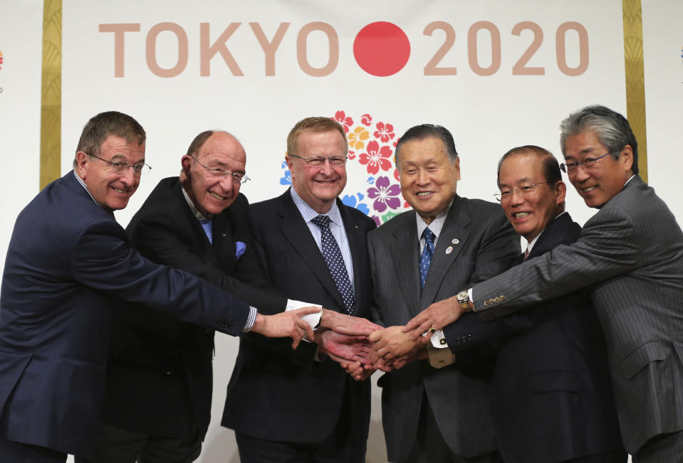 FILE - In this April 4, 2014, file photo, From left, then International Olympic Committee (IOC) Executive Director Gilbert Felli, IOC member Alex Gilady, IOC Vice President John Coates, Yoshiro Mori, president of the Tokyo Organizing Committee of the Olympic and Paralympic Games, Toshiro Muto, Chief Executive Officer of Tokyo 2020, and then Japan's Olympic supremo Tsunekazu Takeda pose for photographers at IOC/ TOKYO 2020 Joint Press Conference in Tokyo. Mori resigned Friday, Feb. 12, 2021 as the president of the Tokyo Olympic organizing committee following sexist comments implying women talk too much. (AP Photo/Eugene Hoshiko, File)