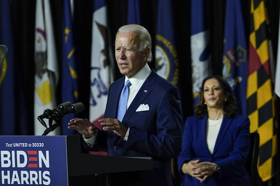 Presumptive Democratic presidential nominee former Vice President Joe Biden (L) speaks as his running mate Sen. Kamala Harris (D-CA) looks on during an event in Wilmington, Delaware.