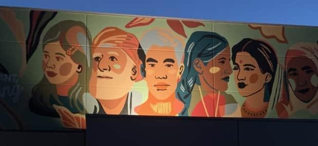 The new mural in Summerland features faces representing the diverse backgrounds of people living in the community. (Submitted by Dylan Ranney - image credit)