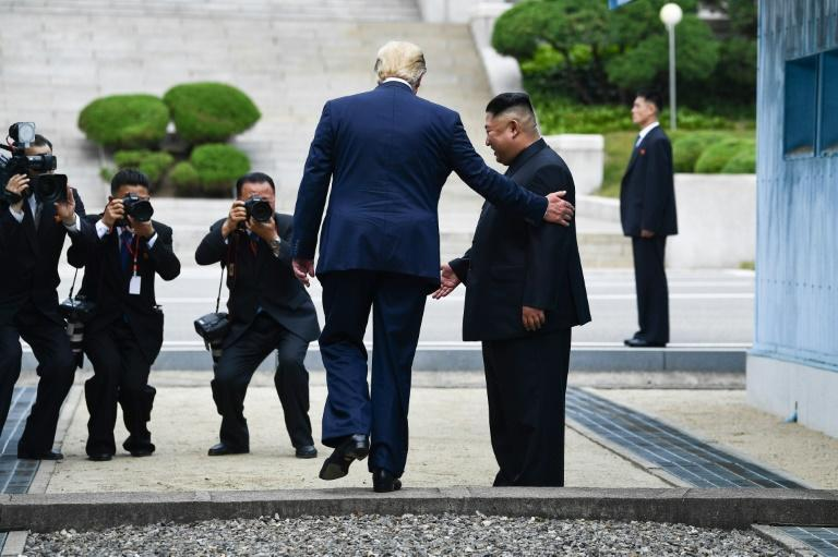 US President Donald Trump steps into the northern side of the Military Demarcation Line that divides North and South Korea, as Kim Jong Un looks on, in Panmunjom in the Demilitarized zone (DMZ) on June 30, 2019