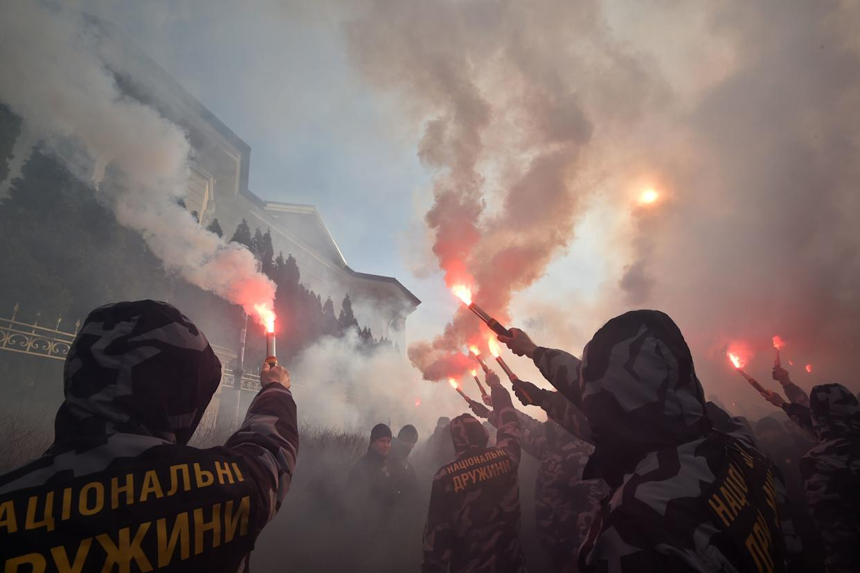 Activists and supporters of the Ukrainian far-right party National Corps burn flares in front of the private house which supposedly belongs to Svynarchuk in Kiev region on March 3, 2019. - Svynarchuk is the surname of the father and son, which translating to English as a pig, accused of allegedly enriching themselves by smuggling military equipment from Russia to Ukraine. On February 25, an independent media outlet aired a report alleging that people close to the president had smuggled parts for military equipment from Russia, causing the head of state, who faces a tough re-election bid next month, to come under fire. Accusations of ties involving Russia are extremely sensitive in Ukraine which has battled against Moscow-backed separatists since 2014, in a conflict that has claimed some 13,000 lives. (Photo by Genya SAVILOV / AFP) (Photo credit should read GENYA SAVILOV/AFP/Getty Images)