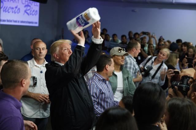 <p>President Donald Trump tosses paper towels into a crowd as he hands out supplies at Calvary Chapel, Tuesday, Oct. 3, 2017, in Guaynabo, Puerto Rico. Trump is in Puerto Rico to survey hurricane damage. (Photo: Evan Vucci/AP) </p>
