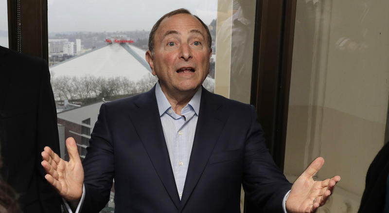With KeyArena over his shoulder in the window at left, NHL Commissioner Gary Bettman talks to visitors Wednesday, Jan. 9, 2019, at a luncheon prior to a news conference in Seattle. Bettman said Wednesday the NHL has promised Seattle it will host the hockey All-Star Game within its first seven seasons, with the team slated to begin play in 2021-22 in a renovated KeyArena. Bettman also said Seattle will host the NHL draft, likely before the All-Star Game arrives. (AP Photo/Ted S. Warren)