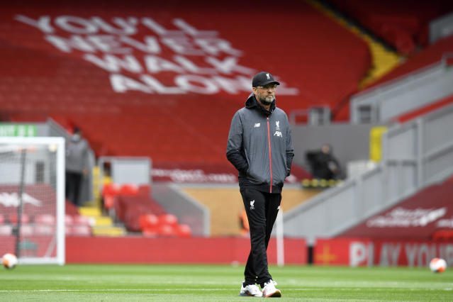 Liverpool's manager Jurgen Klopp walks on the pitch during warmup before the English Premier League soccer match between Liverpool and Aston Villa at Anfield Stadium in Liverpool, England, Sunday, July 5, 2020. (Paul Ellis/Pool via AP)