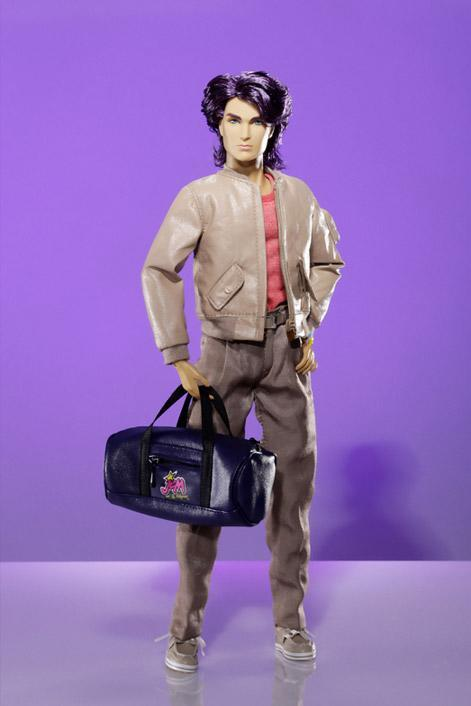 """<div class=""""caption-credit""""> Photo by: Hasbro/Integrity Toys</div><b>New Rio</b> <br> Rio has been vastly improved in his pleather varsity jacket (with working tiny zippers), deck shoes, and high-waisted pleated pants (hello, '80s). The new doll may not be as colorful as the original, but this is an outfit Rio often wore on the small screen. He also comes with a watch, a Jem duffle bag, backstage pass, and """"concert hall layout schematics."""" These collectible dolls are not messing around."""
