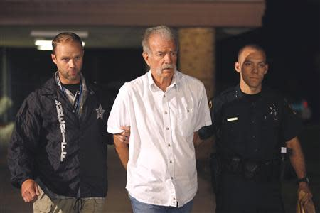 Pastor Terry Jones is escorted by Polk County Sheriff's Deputies to a waiting patrol car at their PCSO Southwest District substation in Lakeland, Florida September 11, 2013. REUTERS/Pierre DuCharme