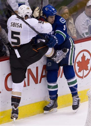 Anaheim Ducks defenseman Luca Sbisa (5) and Vancouver Canucks right wing Zack Kassian (9) go into the boards during first period NHL hockey action at Rogers Arena in Vancouver, British Columbia, Tuesday, April, 3, 2012. (AP Photo/The Canadian Press, Jonathan Hayward)