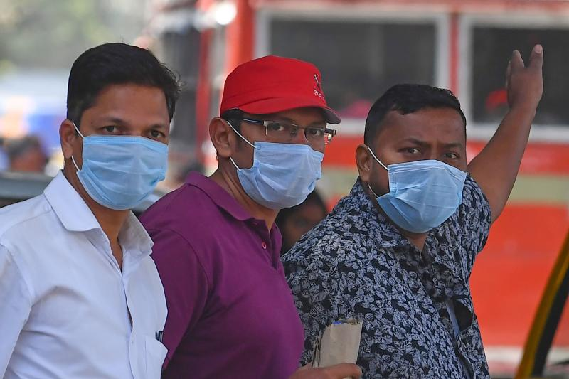 Men wearing facemasks amid concerns of the spread of the COVID-19 coronavirus stand outside a hospital, in Mumbai on March 12, 2020. (Photo by Indranil MUKHERJEE / AFP) (Photo by INDRANIL MUKHERJEE/AFP via Getty Images)