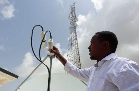 A Somali Optical Network technician checks a satellite dish at their headquarters in Mogadishu