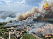 In this photo released by the Italian Firefighters, a view of a violent wildfire that burned the historical pinewood in Pescara, central Italy, Sunday, Aug. 1, 2021. Sea resorts customers were seen running away as the flames were approaching the beach. More than 100 people were evacuated from their houses. A heat wave across southern Europe, fed by hot air from North Africa, has led to wildfires across the Mediterranean, including on the Italian island of Sicily and in western Greece. (Italian Firefighters via AP)