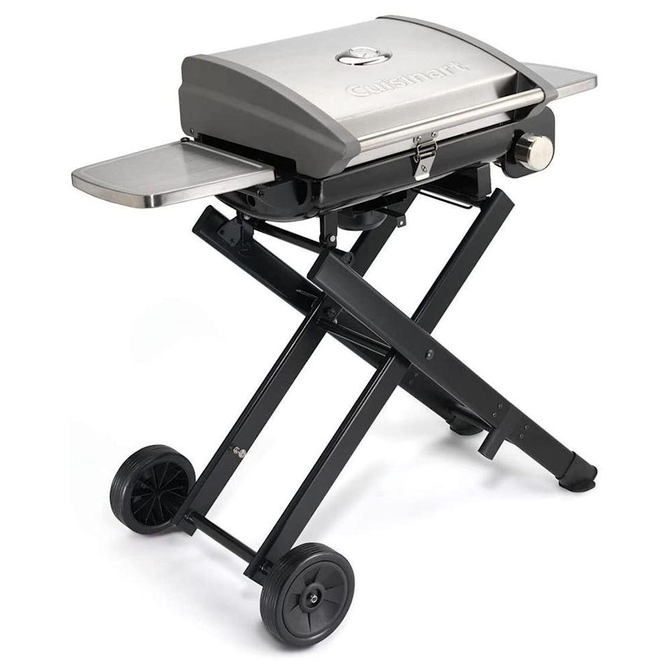 """<p><strong>Cuisinart</strong></p><p>amazon.com</p><p><strong>$226.78</strong></p><p><a href=""""https://www.amazon.com/dp/B0932SCZKC?tag=syn-yahoo-20&ascsubtag=%5Bartid%7C2089.g.36490432%5Bsrc%7Cyahoo-us"""" rel=""""nofollow noopener"""" target=""""_blank"""" data-ylk=""""slk:Shop Now"""" class=""""link rapid-noclick-resp"""">Shop Now</a></p><p>There's no need to awkwardly carry this gas grill from place to place. It folds down and rolls away like a piece of luggage. To make things even more convenient, it still offers two swing-out shelves and an 18 x 13-inch cast-iron grate with enough room to cook (and flip) 12 burgers. Its stainless steel build and generous warranty ensure it'll last for your future camping trips.</p>"""