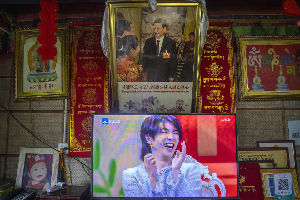 """FILE - In this June 4, 2021, file photo, a television shows a broadcast of a Chinese talk show program as it sits beneath a photo of Chinese President Xi Jinping in a home converted into a tourist homestay in Zhaxigang village near Nyingchi in western China's Tibet Autonomous Region. China's government banned effeminate men on TV and told broadcasters Thursday, Sept. 2, 2021 to promote """"revolutionary culture,"""" broadening a campaign to tighten control over business and society and enforce official morality. (AP Photo/Mark Schiefelbein, File)"""
