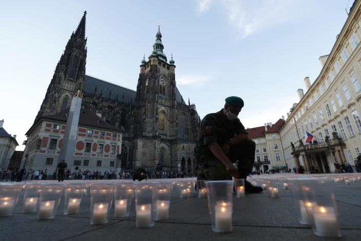 A soldier lights up a candle to commemorate victims of the COVD-19 pandemic at the Prague Castle in Prague, Czech Republic, Monday, May 10, 2021. The Czech Republic is massively relaxing its coronavirus restrictions as the hard-hit nation pays respect to nearly 30,000 dead. (AP Photo/Petr David Josek)