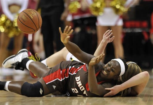 Brown's Sheila Dixon passes the ball after struggling with Maryland's Tierney Pfirman, partially blocked, during the second half of an NCAA college basketball game, Friday, Dec. 28, 2012, in College Park, Md. Maryland won 76-36.(AP Photo/Gail Burton)
