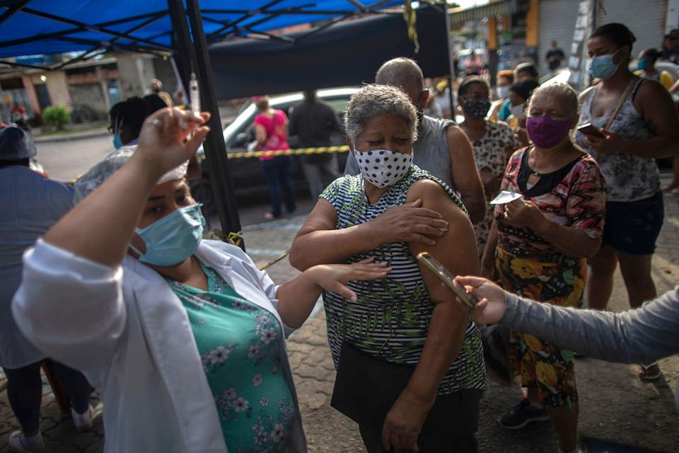 A woman is seen after receiving a dose of the COVID-19 vaccine at a vaccination center on Cangulo square, Saracuruna neighbourhood, in Duque de Caxias, Rio de Janeiro state, Brazil, on March 30, 2021. (Photo by Mauro Pimentel / AFP) (Photo by MAURO PIMENTEL/AFP via Getty Images)