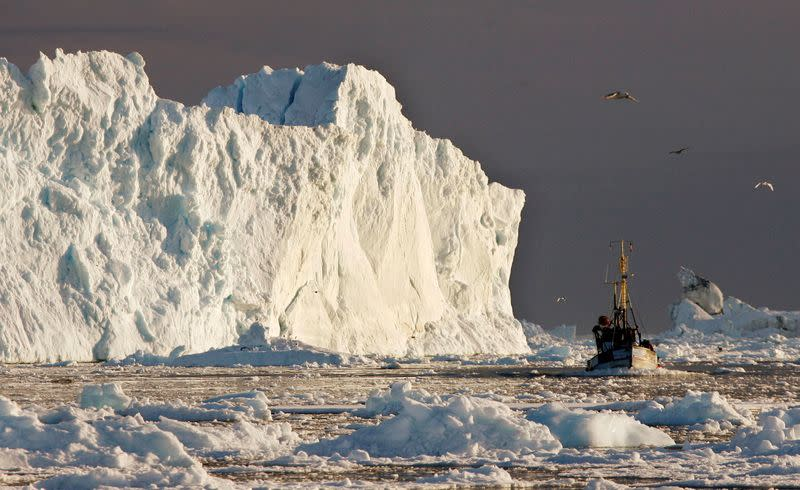 FILE PHOTO: A fishing boat sails past a large iceberg at the mouth of the Jakobshavns ice fjord near Ilulissat