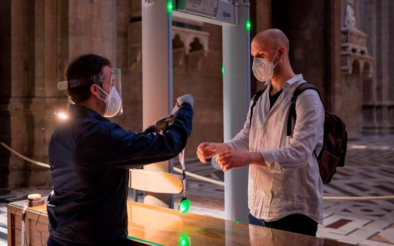 an attendant (L) handing to a visitor a new device that allows to maintain a safe distance between visitors, during testing on the eve of the museum's and Florence's Duomo reopening as the country eases its lockdown - FLORENCE MUSEUM PRESS OFFICE/AFP via Getty Images