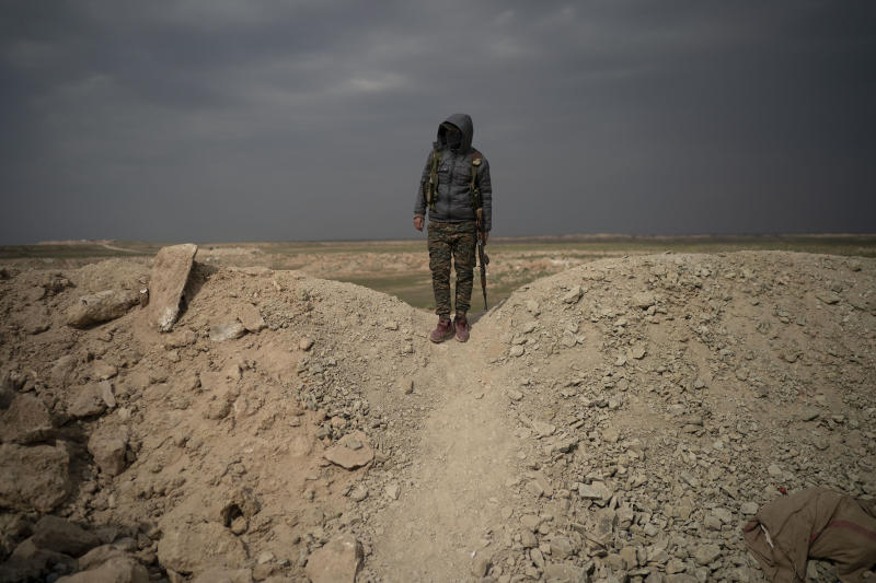 A U.S.-backed Syrian Democratic Forces (SDF) fighter stands atop a hill in the desert outside the village of Baghouz, Syria, Thursday, Feb. 14, 2019. U.S.-backed Syrian forces are clearing two villages in eastern Syria of remaining Islamic State militants who are hiding among the local population, and detaining others attempting to flee with the civilians, the U.S.-led coalition said Thursday. (AP Photo/Felipe Dana)