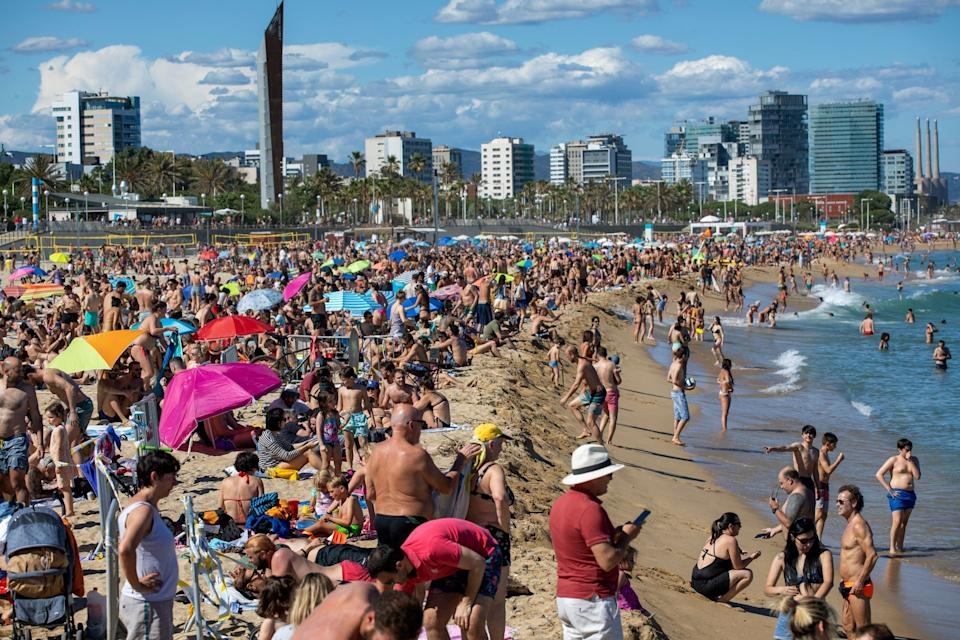 People enjoy the warm weather on the beach in Barcelona, Spain: AP