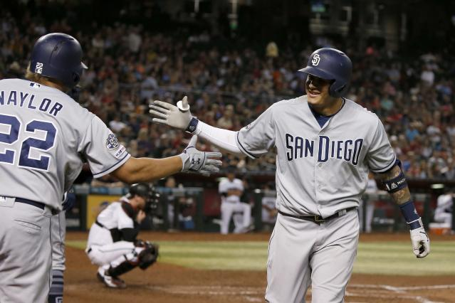 San Diego Padres' Manny Machado, right, celebrates his home run against the Arizona Diamondbacks with teammate Josh Naylor (22) during the sixth inning of a baseball game Friday, Sept. 27, 2019, in Phoenix. (AP Photo/Ross D. Franklin)