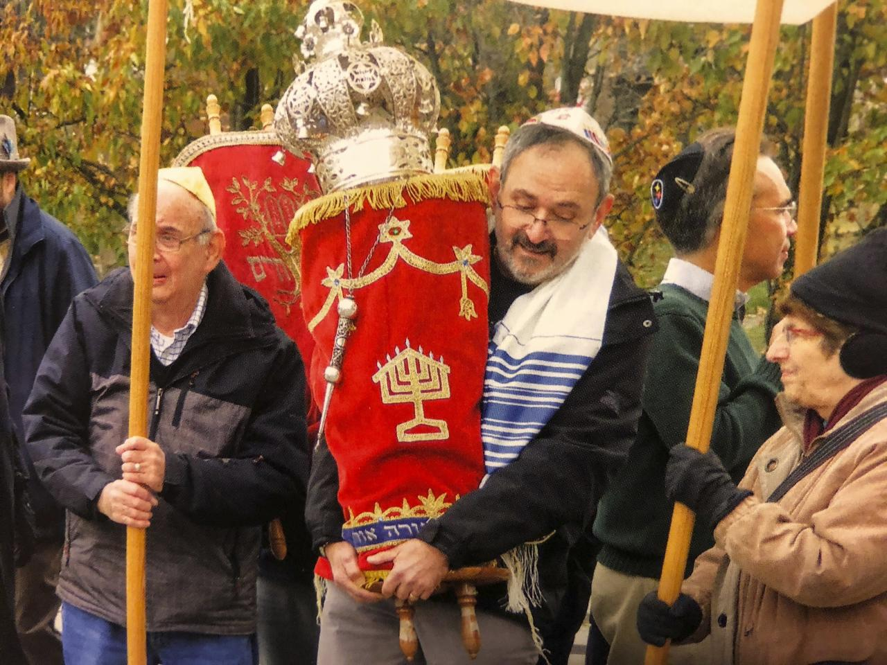 "<p>Gottfried (pictured centre, holding the Torah) was a dentist and also an ""avid golfer, runner and book lover,"" according to USA Today. Not only had he completed the 10-kilometre Great Race, he volunteered with the Catholic Charities Free Dental Clinic with his wife, Margaret Duranchko, the publication reports.<br />(Photo from The Associated Press) </p>"