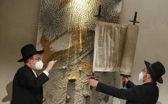 Rabbi Shaul Nekrich, right, holds the Sulzbach Torah Scroll in a ceremony at the Reichstag building in Berlin, Germany, Wednesday, Jan. 27, 2021 to complete the historic Sulzbach Torah Scroll from 1792, rediscovered in 2013 and just restored. The ceremony takes place on the International Holocaust Remembrance Day. (Odd Andersen/Pool Photo via AP)