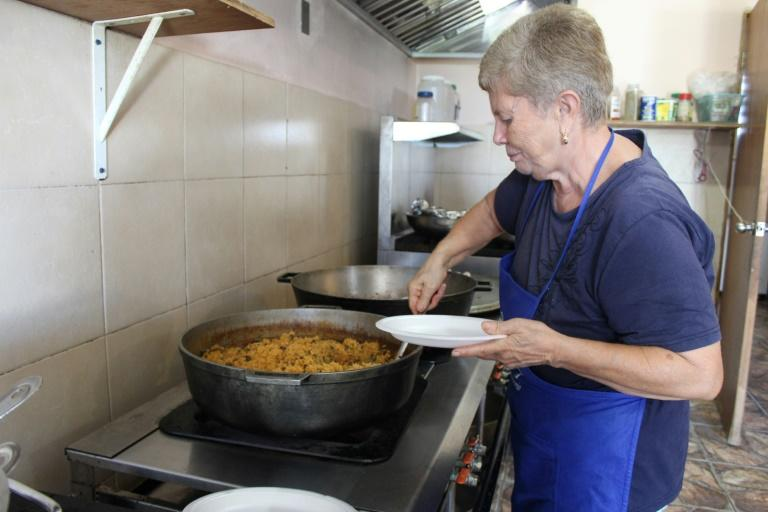 A volunteer prepares meals of rice and pigeon peas in a community kitchen in Mariana, a neighborhood in the town of Humacao that was hard-hit by Hurricane Maria neighbors opened after September 20, 2017