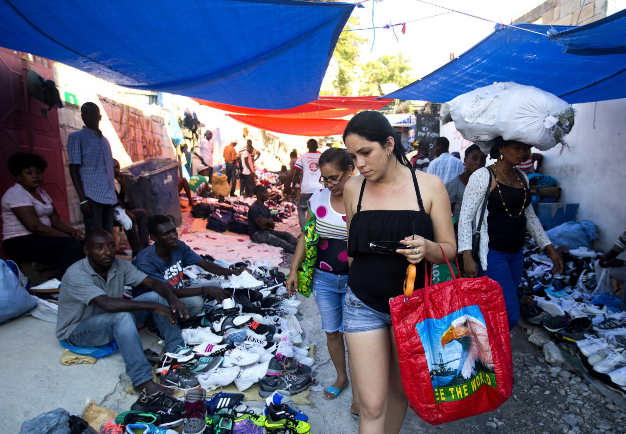 "Cuban women shop at a street market in Port-au-Prince, Haiti, Thursday, Dec. 6, 2018. The ""Cuban market"" in Port-au-Prince is part of a global trade, estimated to top $2 billion, fed by the confluence of Cubans' increased freedom to travel with the communist state's continued domination of the economy back home. (AP Photo/Dieu Nalio Chery)"
