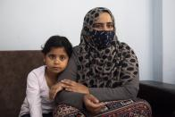 Kariman, 32, sits on a couch with her daughter Layan at their apartment in the northern city of Thessaloniki, Greece, Saturday, May 1, 2021. Sundered in the deadly chaos of an air raid, a Syrian family of seven has been reunited, against the odds, three years later at a refugee shelter in Greece's second city of Thessaloniki. (AP Photo/Giannis Papanikos)
