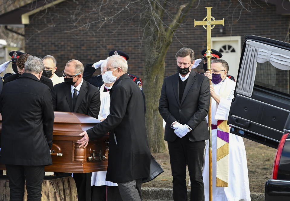 Hockey hall-of-fame legend Wayne Gretzky, second right, cries as he watches the casket of his father, Walter Gretzky, be carried from the church during a funeral service in Brantford, Ontario, on Saturday, March 6, 2021. Walter Gretzky also know as Canada's hockey dad was 82 years-old. (Nathan Denette/The Canadian Press via AP)
