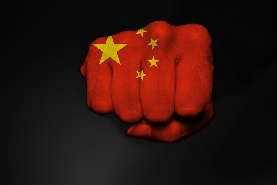 Low key picture of a fist painted in colors of a China flag on a black backround
