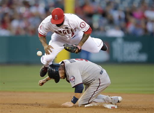 Los Angeles Angels' Howie Kendrick, top, loses the ball as he jumps over Minnesota Twins' Ryan Doumit after forcing him out during the second inning of a baseball game on Monday, July 22, 2013, in Anaheim, Calif. (AP Photo/Jae C. Hong)