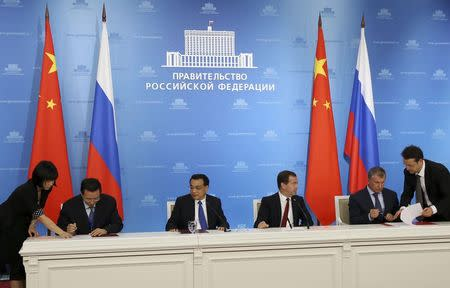 Russia's Prime Minister Dmitry Medvedev (3rd R), China's Premier Li Keqiang (3rd L), Rosneft President Igor Sechin (2nd R) and CNPC Vice-President Wang Dongjin (2nd L) attend a signing ceremony in Moscow, October 13, 2014. REUTERS/Yekaterina Shtukina/RIA Novosti/Pool