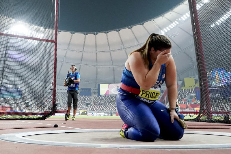 Deanna Price, of the United States, kneels at the throwing circle after winning the gold medal for the women's hammer throw at the World Athletics Championships in Doha, Qatar, Saturday, Sept. 28, 2019. (AP Photo/David J. Phillip)